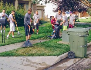 Members of the Berthoud High School football team cleanup a neighborhood after the July 14 hailstorm left debris scattered all over the streets and sidewalks.  John Hall / The Surveyor