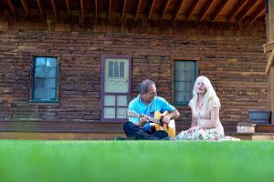 Butch Hause, left and his wife, Sarah Lincoln, play around in their backyard in front of the stage that has housed critically acclaimed musicians every August as part of the annual Farm Concert. John Gardner / The Surveyor