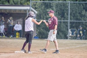 Hannah Langer gets a fist bump from assistant coach Anthony Heronema after making it safely to third base in the home opener against the Thompson Valley Eagles on Aug. 22. John Gardner / The Surveyor