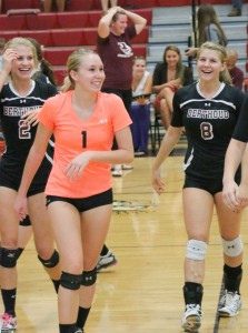 Alyssa Peacock, left, Haley Hummel, center, and Jessa Megenhardt, right, with coach Agho in the background, show their emotions with the win over Erie in 5 sets on Sept. 25. Paula Megenhardt / The Surveyor
