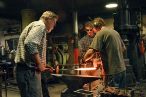 Mark French and David Norrie take the red-hot iron bar from the furnace and hammer a punch through to make a square shaped opening in the center of bar that will eventually allow another bar to pass through when assembled. May Soricelli / The Surveyor