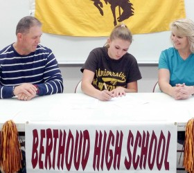 Berthoud High School's Kiah Leonard, center, with her mother, Kristi Leonard, right, and father, Dale Leonard, left, signs her letter of intent to join the University of Wyoming's cross country team and attend as a student next fall. John Hall / The Surveyor