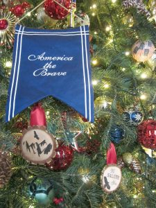 """An ornament displays the Christmas tree's theme, """"America the Brave,"""" honoring all the men and women who have served in the U.S. military."""