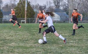 Berthoud striker Jade Glasser races toward the goal with Mead defenders in pursuit during the first period of the March 30 game at Berthoud High School. Despite the Spartans' best efforts, the game ended in a 0-0 tie after two overtime periods. John Gardner / The Surveyor