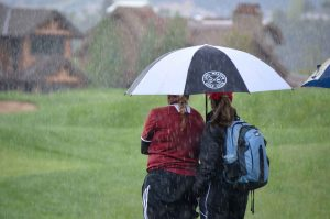Berthoud's Molli Boruff and coach Mary Durkin take shelter under an umbrella as the rain comes down on the 14th hole at River Valley Ranch in Carbondale Tuesday during the girls 4A State Golf Championship. The wet and cold weather made for some challenging golf at the state tournament. Colleen O'Neil / Special to The Surveyor