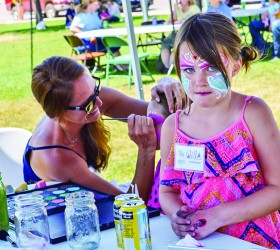 Willa Schump is a volunteer for the day helping her mom, Maggie Schump, with face painting. It was a family affair, Willa's grandmother is Habitat store manager Sharon Derstine. Sharon's son Andrew Gingerich was also at the event grilling the free hot dogs for the event.  May Soricelli / The Surveyor