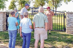 Pauli Driver-Smith tells Backroads travelers about the Highlandlake Cemetery gate at the Highland Cemetery on July 11. The gate was a relatively recent addition to the historical landmark. May Soricelli / The Surveyor