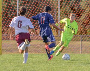 Berthoud goal keeper Hunter Hursey charges a Northridge opponent to save a goal in the first half of the Sept. 1 game at Berthoud High School. John Gardner / The Surveyor