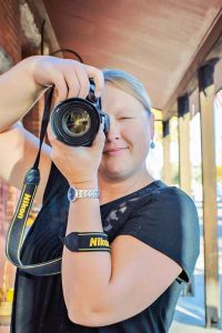 """Berthoud resident and photographer RaeLynn Petrovich is caught in the moment taking a photo on Mountain Avenue. Petrovich started a photography business """"Second Shot"""" after being diagnosed with cancer in 2010. May Soricelli / The Surveyor"""