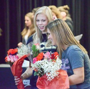 Alyssa Strong, left, and Josie Spitz receive flowers from family after signing their letters of intent on Nov. 11 in the BHS commons. John Gardner / The Surveyor
