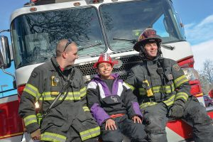 Cisco Debevec sits on the front of the Fire Engine with firefighters Andy Berger, left, and Captain Andrew Kuiken, right. The Surveyor
