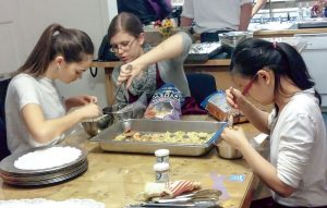 Lauren Dietz, left, Teagan Ives, center, and Jordan Crout, right, prepare food for an event.