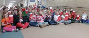 Berthoud Elementary School first and second graders pose for a photo in the school's hallway to show off their Christmas stockings that they put together for veterans through the Soldiers' Angels program, with help from the Berthoud American Legion Auxiliary Justin Bauer Memorial Post 67, which provides stockings for U.S. military veterans. The Berthoud El students provided over 100 stockings for veterans in need this holiday season. Katie Harris / The Surveyor