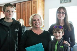 Robin Fancis smiles for a photo with her two sons, Joshua, 15, left, and Caleb, 13, right, and Kim Land of Grace Place Church, during a home dedication on Jan. 23. Angie Purdy / The Surveyor