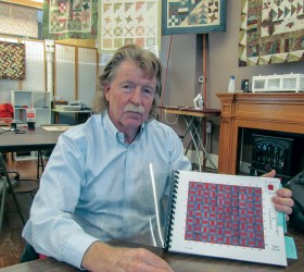 Richard Boston shows the booklet that documents his great-great grandmother's Civil War quilt. Bob McDonnell / The Surveyor