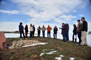A group involved in one way or another with the deal for Larimer County to purchase the Malchow farm listen to Peggy Malchow Sass talk about a pioneer grave that has been on the farm since the mid 1800s. A grave marker was placed some time ago by the Berthoud Historical Society. John Gardner / The Surveyor