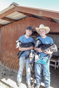 Kira Scoma, 12, and her brother Tucker Scoma, 14, hold two of their week-old Nubian goats. Guests at Guided Hope can enjoy the goats, along with horses, cows, chickens, ducks, rabbits, and llamas during their visits. Photo by Katie Harris / The Surveyor
