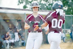 Berthoud's Morgan Schachterle (24) is congratulated by teammate Sotera Dageenakis as she crosses home plate during the home opener against Roosevelt on Aug. 25. The Spartans won the game 12-2. John Gardner / The Surveyor