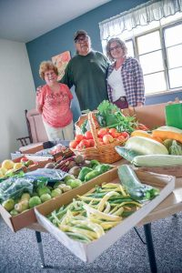Kelly Hines Keller, right, from Plant A Row for the Hungry is photographed with First Presbyterian Church members Sally Seitz, left, and Donald Houle, center. Keller delivers extra produce grown locally to the House of Neighborly Services that operates out of the church on Tuesdays. Houle and Seitz contribute produce grown at the church. All the food goes to families in need.  John Gardner / The Surveyor