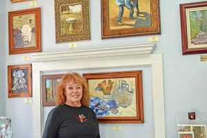 Homestead Fine Art Gallery's Peggy Keagle stands by some of her art in the gallery she shares with nine other artists. Bob McDonnell / The Surveyor