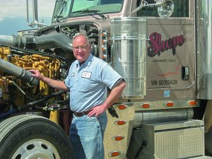 George Wood pictured near one of the trucks he spent his career working on. Courtesy Heavy Duty Truck Repair